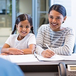 Smiling mother and daughter checking in at dental reception desk