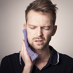 man holding jaw with dental emergency