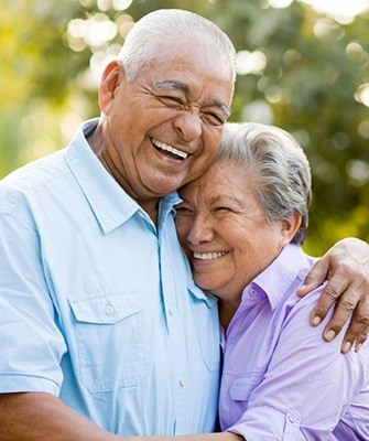 Older man and woman laughing together outdoors
