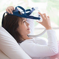 Woman placing CPAP mask