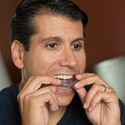 Man placing oral appliance