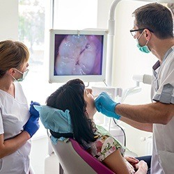 Dental team and patient looking at intraoral images