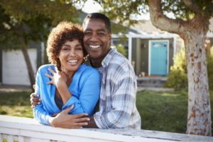 older couple smiling with dental implants in Westhampton