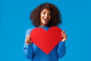 woman smiling and holding a heart for heart health month