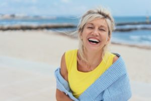 woman smiling after taking summer oral health tips