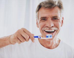 elderly man brushing his teeth and following dental hygiene tips